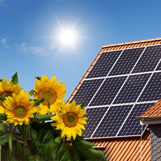haus-mit-photovoltaik-zellen-auf-dach-und-sonnenblumen-sommer Photovoltaik-Anlage im Sommer